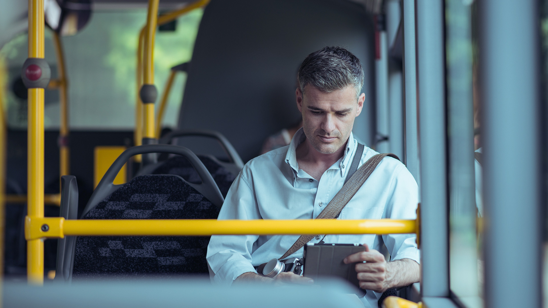 Man looking at tablet on bus